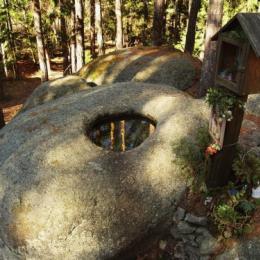 V žulových kameňoch v háji sa v mise leskne hladina vody. Cestu lemujú kaplnky s posvätnými obrázkami. Zdroj: http://www.lideazeme.cz/clanek/pribeh-kukuloviteho-balvanu